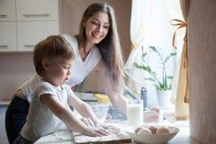 母亲和年轻儿子在厨房里准备一个蛋糕 免版税库存照片
