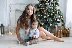 母亲和年轻儿子在家在圣诞树附近 免版税图库摄影