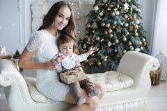 母亲和年轻儿子在家在圣诞树附近 库存照片