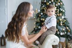 母亲和年轻儿子在家在圣诞树附近 库存图片
