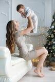 母亲和年轻儿子在家在圣诞树附近 图库摄影
