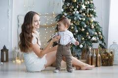 母亲和年轻儿子在家在圣诞树附近 免版税库存照片