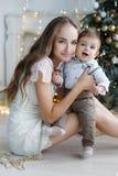 母亲和年轻儿子在家在圣诞树附近 免版税库存图片
