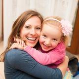 母亲和年轻女儿戏剧在客厅 库存图片