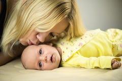 母亲和婴孩亲吻,拥抱 免版税库存图片