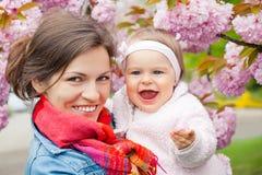 母亲和婴孩在庭院里 库存图片