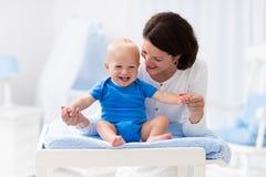 母亲和婴孩在改变的桌上 库存图片