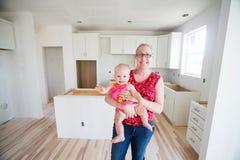 母亲和婴孩在新的家庭建筑 免版税库存照片