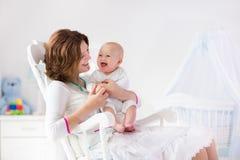 母亲和婴孩在白色卧室 库存照片