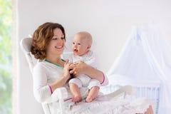 母亲和婴孩在白色卧室 图库摄影