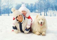 母亲和婴孩有白色萨莫耶特人的在雪一起尾随在冬天 免版税图库摄影