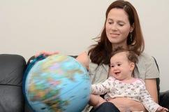 母亲和婴孩查寻和审查地球 免版税图库摄影