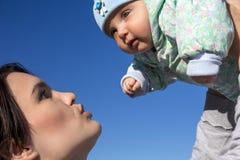 母亲和婴孩蓝天背景的 库存图片