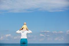 母亲和婴孩观察cloudscape和海 库存照片