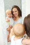 母亲和婴孩镜子的反射在卫生间里 免版税库存图片
