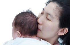 母亲和婴孩,基于她的mother& x27的可爱的亚裔女孩; s shoul 库存图片