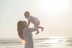 母亲和婴孩画象海滩的在日落 库存图片