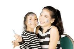 母亲和他的女儿绘了他们的面孔 免版税库存图片