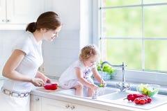 母亲和cury卷曲小孩洗涤的菜 免版税库存图片
