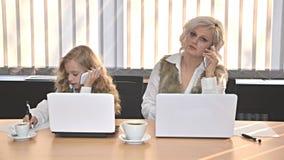 母亲和daugter与运转在办公室的膝上型计算机 库存照片