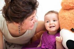 母亲和dauhter笑,当使用与熊时 库存图片