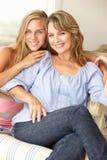 母亲和ome的十几岁的女儿在沙发 免版税库存图片