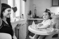 年轻母亲哺养的女儿 库存图片