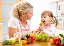 母亲哺养的孩子菜在厨房里 库存照片