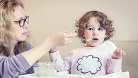 母亲喂养她的有匙子的可爱宝贝 库存图片