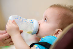 母亲喂养从一个瓶的婴孩牛奶 库存图片