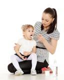 年轻母亲喂养她的婴孩。 库存照片