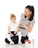 年轻母亲喂养她的婴孩。 免版税库存图片