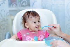母亲喂养有匙子的婴孩 免版税库存图片