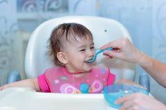 母亲喂养有匙子的婴孩 免版税图库摄影