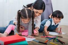 母亲图画班的教学孩子 与五颜六色的蜡笔颜色的女儿和儿子绘画在家 师范训练学生 免版税库存图片
