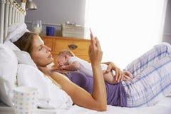 母亲在与检查手机的小女儿的床上 库存图片