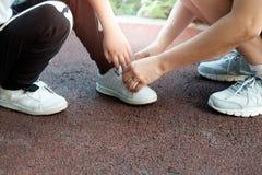 母亲在公园帮助他的儿子栓他的鞋子 免版税库存图片