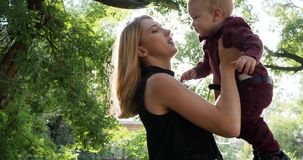 母亲在公园,愉快的家庭休息拿着在手上的小儿子在背景绿色树的背后照明 股票视频