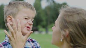 母亲在她的儿子的面孔上把防护奶油放,孩子不喜欢 股票视频