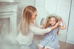 母亲在她的女儿上把一个花卉花圈放 库存图片