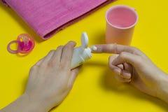 母亲在婴孩刷子上把牙膏,掠过的牙,牙刷放 免版税图库摄影