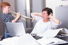 母亲在家庭办公室,儿子工作通过演奏t打扰 库存图片