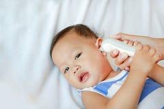 母亲在家采取男婴的温度有在床上的耳朵体温计的 免版税库存图片