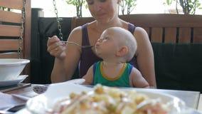 年轻母亲在意大利喂养她的膝部面团的婴孩 哄骗1年,它在一件绿色T恤杉 股票录像