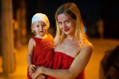 母亲在晚上拿着她的胳膊的女儿,有女儿的母亲穿戴在红色礼服,白色贝雷帽的孩子, 免版税库存图片