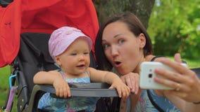 母亲在有一个婴孩的一个手机做selfie婴儿推车的 股票视频