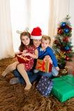 年轻母亲在有儿子和女儿的圣诞老人帽子 免版税库存图片