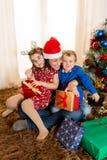 年轻母亲在有儿子和女儿的圣诞老人帽子 库存图片