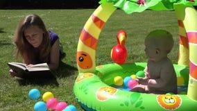 母亲在格子花呢披肩读了书并且照看小家伙水池的小女儿 4K 股票视频