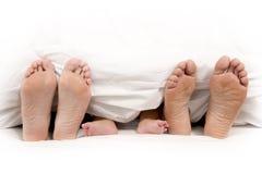 母亲在毯子下的父亲和婴孩脚 库存图片
